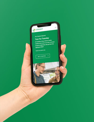 A hand holding an iPhone with a green background. The iPhone shows a website for chiropractic services.