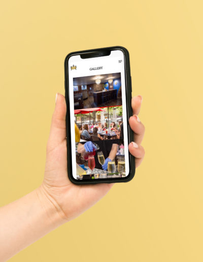 A hand holding a phone with a yellow background showing a fine dining gallery of images.