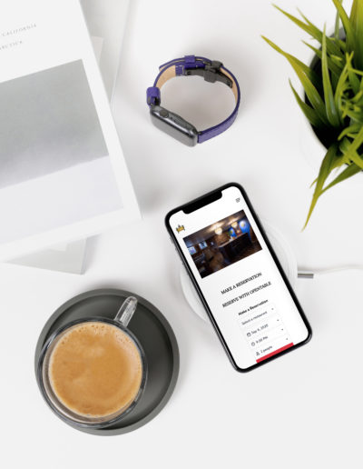 A mobile phone on a marble desk next to a cup of coffee, a plant, and a smartwatch.