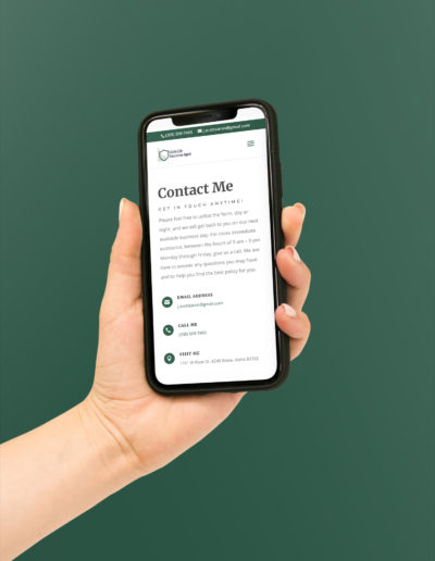 A hand holding a phone showing the contact page of the insurance website.