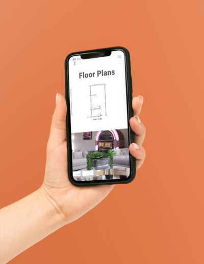 A hand holding an iPhone showing floor plans for an assisted living website.