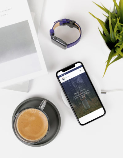A phone sitting on a table featuring the homepage of the spiritual guidance website.