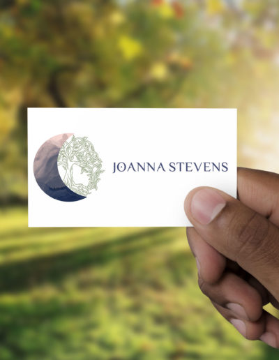 A logo featuring a moon, tree of life, and name, held on a card by a man.